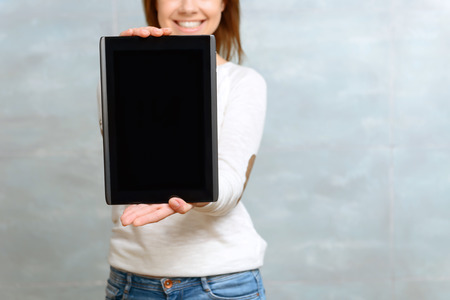 Close up of tablet showed by smiling woman on isolated background.