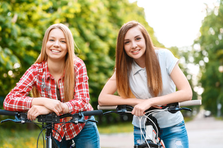 handlebars: Young beautiful girl with brown hair together with her blond pretty friend standing leaning on the handlebars of their bikes smiling in the green park Stock Photo