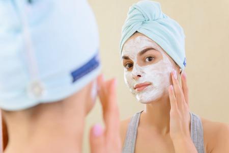きれいだね。 彼女の顔を鏡で見ている美容マスクを持つ少女のクローズ アップ。