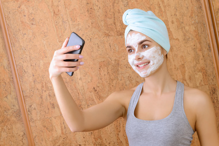female mask: Funny selfie. Girl doing selfie with white clay beauty mask on face.