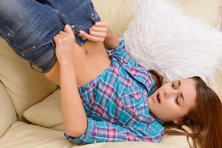 Crazy girls. Hard trying of girl to get into new jeans. Stock Photo