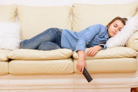 Boring film. Girl sleeping on sofa ta home in front of TV. Zdjęcie Seryjne