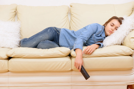 sofa television: Boring film. Girl sleeping on sofa ta home in front of TV. Stock Photo