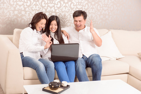 Family time.  Sitting at home happy Asian family chatting on skype Stock Photo