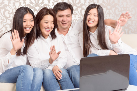 skype: Connecting people. Asian family chatting on skype at home
