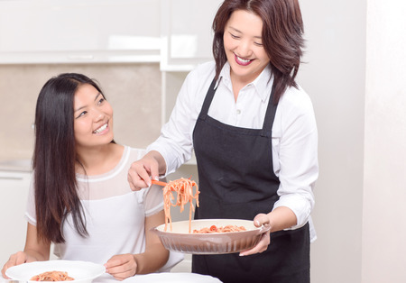 Mommy cooks the best.  Asian mother bringing up fresh dish to her daughter