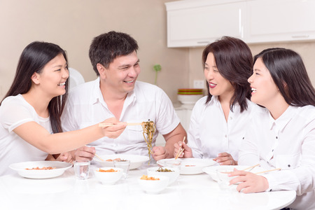 close together: As at home.  Asian family finally home all together and eating Stock Photo