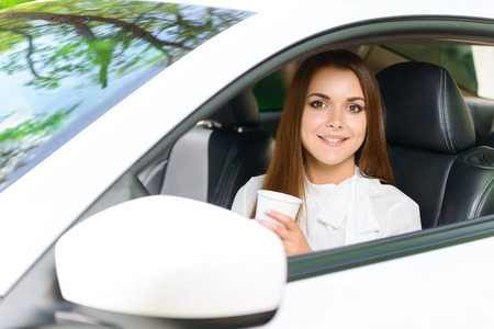 youthful: Having rest. Pretty youthful smiling woman sitting in car and holding white paper cup