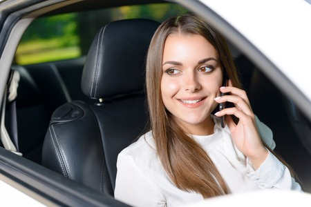 youthful: Pleasant conversation. Beautiful youthful woman sitting in car an talking per mobile phone.