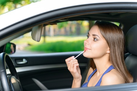 youthful: Glossing over. Beautiful youthful lady sitting inside car and putting lip gloss on her lips.