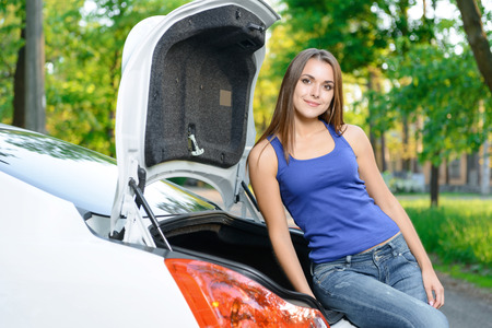lean machine: Taking rest. Pleasant young slim woman leaning on opened boot of white car Stock Photo