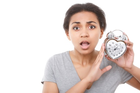mulatto: Oh my god. Portrait of youthful pleasant mulatto girl holding alarm clock near her face on white isolated background.