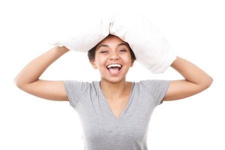wellness sleepy: Having fun. Young smiling lady standing with white pillow on her head against isolated background Stock Photo