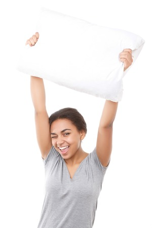 youthful: With winking. Pretty youthful mulatto lady standing against isolated background and holding white pillow up