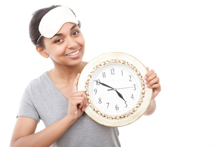 get tired: Time to go. Beautiful young smiling lady holding big clock on white isolated background