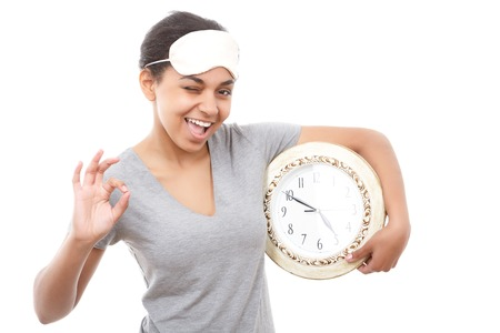 get tired: Everything is ok. Winking smiling woman holding big clock against white isolated background and pointing ok Stock Photo