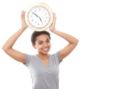 get tired: Feeling funny. Funny young mulatto girl holding big clock above her head on white isolated background