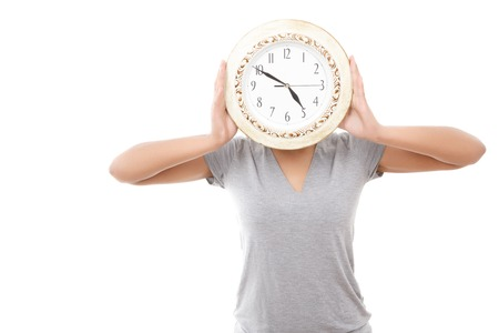 mulatto woman: Missis clock. Pleasant youthful mulatto woman standing with big clock instead of her head against white isolated background Stock Photo