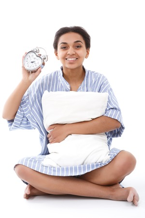 get tired: Time is flying. Pretty youthful lady sitting slightly embracing pillow and holding alarm clock.