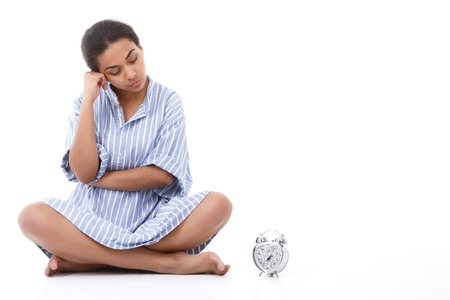 wellness sleepy: Looking thoughtful. Portrait of beautiful young lady sitting on white isolated background and looking at alarm clock next to her