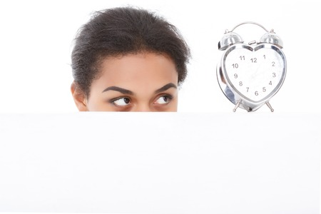 get tired: Looking intently. Attractive youthful mulatto girl on white isolated background having look at alarm clock.