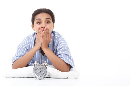 get tired: Looking shocked. Pretty young mulatto girl lying on white pillow against isolated background and covering her mouth with fingers Stock Photo