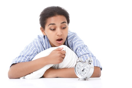get tired: Looking confused. Portrait of young mulatto girl with opened mouth looking at alarm clock