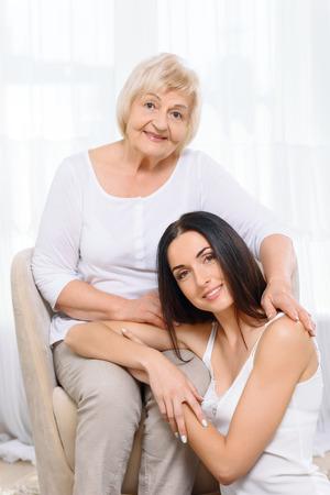 familias unidas: Dos generaciones. Retrato de joven mujer sentada cerca de su abuela en la butaca. Foto de archivo