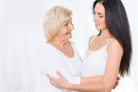 glancing: Soft glance. Pretty grandmother and granddaughter standing and embracing glancing at each other on white background