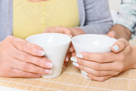 Nice manicure. Close-up of two women holding cups of tea in kitchen