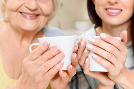Holding still. Smiling grandmother and granddaughter holding cups of tea Stockfoto