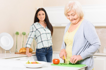 pension cuts: Cooking time. Pretty old woman standing in kitchen and cutting cucumber near her granddaughter.