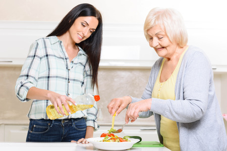 pension cuts: Working together. Two women of different generations standing in kitchen and cooking salad. Stock Photo