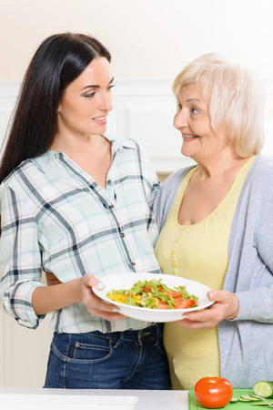 selfmade: Self-made. Granny and her granddaughter standing in kitchen and holding dish with salad. Stock Photo