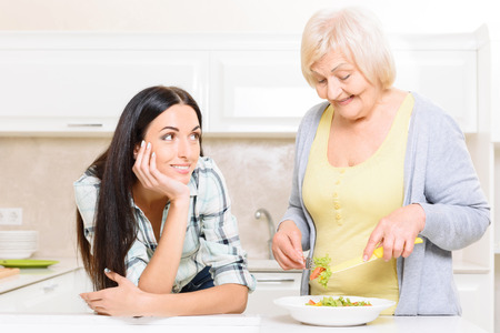 pension cuts: Time for dreaming. Portrait of grandmother standing in kitchen and mixing salad next to her granddaughter. Stock Photo