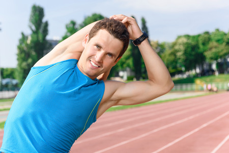 guy standing: Being sportive. Young handsome guy standing and bending hid body in stretching. Stock Photo