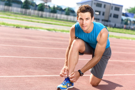 lacing sneakers: Lacing tight. Portrait of young handsome sportsman sitting and lacing his sneakers