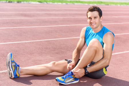 lacing sneakers: Making comfortable. Portrait of young sportsman sitting on floor and lacing his sneakers Stock Photo