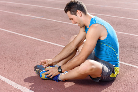 stretch out: Stretch it out. Attractive young sportsman sitting on floor and holding his legs while stretching
