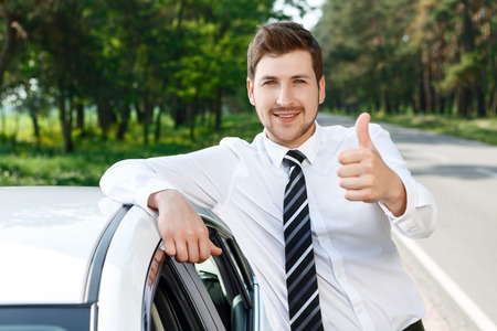 alright: Everything is alright. Portrait of young businessman with beard standing near car and thumbing up.
