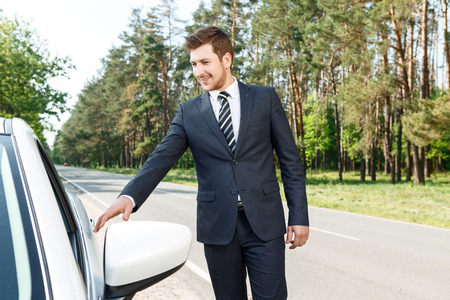 open door: Getting ready. Portrait of young handsome businessman opening his car. Stock Photo