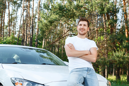 Totally confident. Handsome young man sitting on bonnet of new white car with crossed arms in chest area Stock Photo