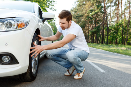 man sad: Looking through. Young attractive man with beard sitting near car and checking tire conditions. Stock Photo