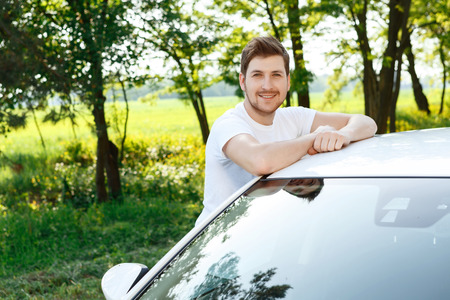 lean machine: Looking happy. Youthful  attractive man with beard leaning on roof of his car and smiling. Stock Photo