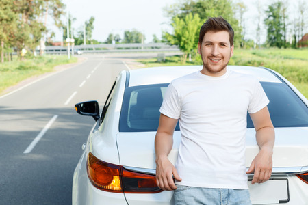 lean machine: This is mine. Handsome happy young man with beard standing behind his new car.
