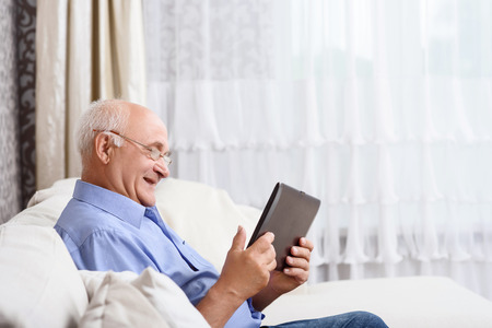 old technology: Using technologies. Portrait of old man sitting on couch and using tablet.