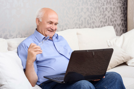 lap top: Watching film. Smiling attractive grandfather sitting on couch holding spectacles and using lap top. Stock Photo