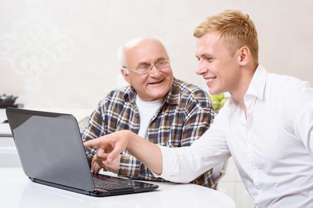 poner atencion: Prestar atenci�n. Nieto se sienta junto a su abuelo en la cocina y que se�ala en la computadora port�til Foto de archivo