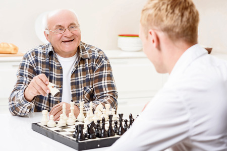 playing chess: I will win. Grandson sitting together with his grandpa in kitchen and playing chess