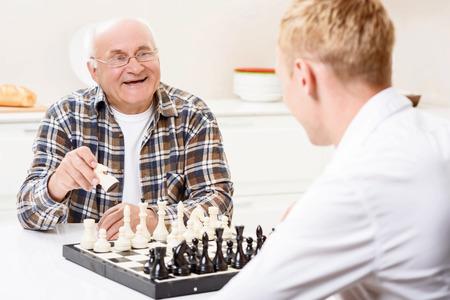 ajedrez: Yo ganaré. Nieto se sienta junto a su abuelo en cocina y jugar al ajedrez Foto de archivo